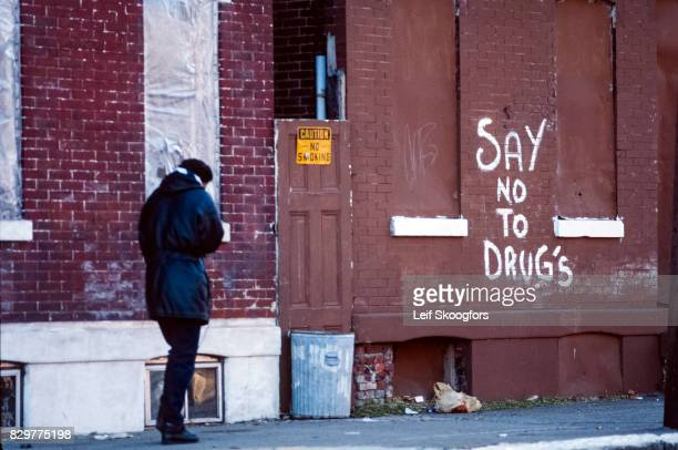 An unidentified pedestrian walks past graffiti that reads 'Say No to Drugs' on brick wall Philadelphia Pennsylvania 1992 Due to a prevalence of...