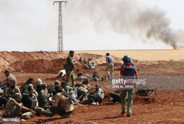 An unidentified photographer stands next to rebel fighters from Jaysh alIslam holding a position behind a sand barrier on August 25 on the frontline...