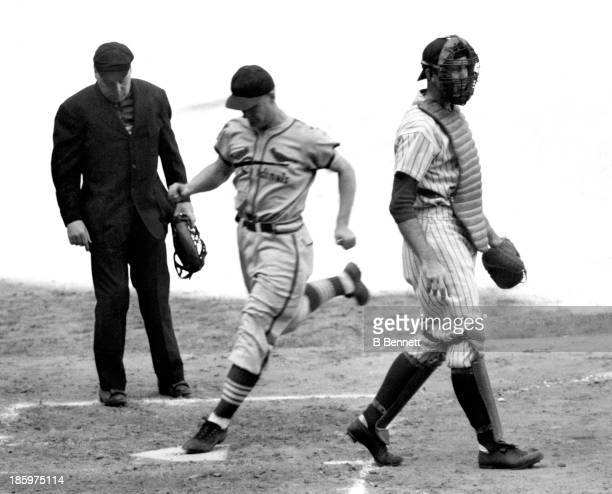 An unidentified player for the St Louis Cardinals scores as catcher Hank Severeid of the New York Yankees follows the play during the 1926 World...