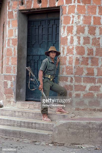 An unidentified Salvadoran guerrilla from the People's Revolutionary Army stands on the steps before a brick building eastern El Salvador May 1 1983...