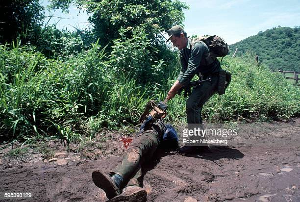 An unidentified Salvadoran soldier of the Atlacatl Battalion pulls an ammunition belt from the corpse of a People's Revolutionary Army guerrilla on a...