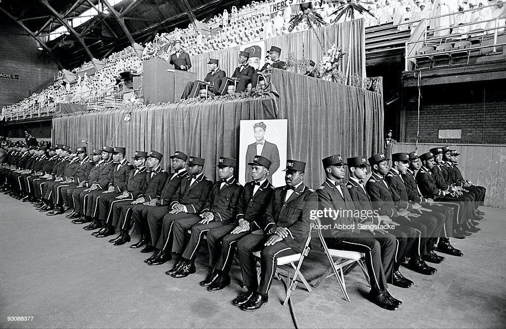 An unidentified speaker stands at a podium, with other seated dignitaries, at the Nation of Islam Saviour's Day celebrations at General Richard Jones Armory, Chicago, Illinois, February 26, 1967. The uniformed men who ring the raised platform wear the uniform of the Fruit of Islam, a subset of the Nation of Islam.