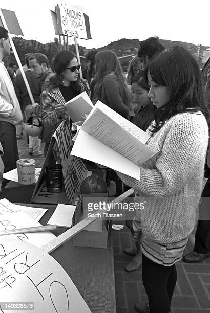 An unidentified student reads from an informational packet during a demonstration on the campus of the University of California Berkeley California...