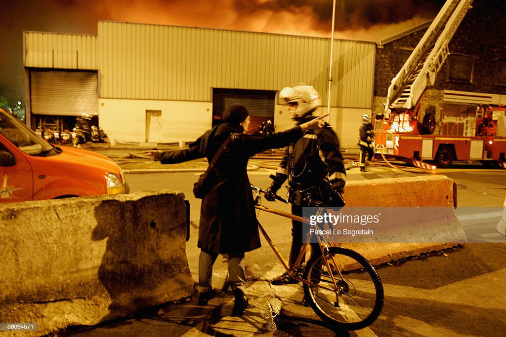 An unidentified talks with a policeman outside a warehouse fire November 4 2005 in Aubervilliers on the outskirts of Paris France Violence was...