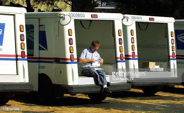An unidentified US Postal Service letter carrier sits on the back of his truck and sorts some letters before heading out to delivery the daily mail...