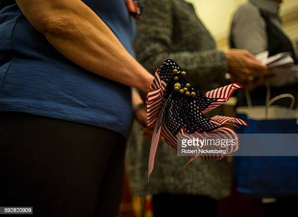 An unidentified volunteer from the American Legion Auxiliary left holds US flags to pass out during a naturalization ceremony for 25 people at the US...
