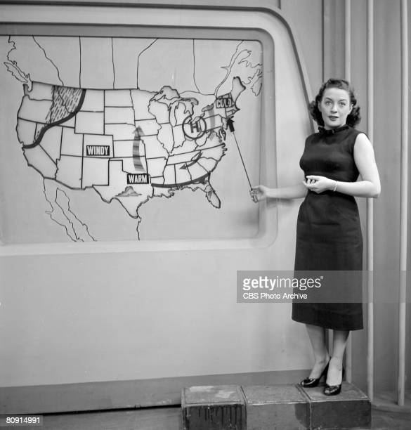 An unidentified weather forecaster stands on a series of boxes as she uses a pointer to highlight a cold weather system on the East Coast during a...