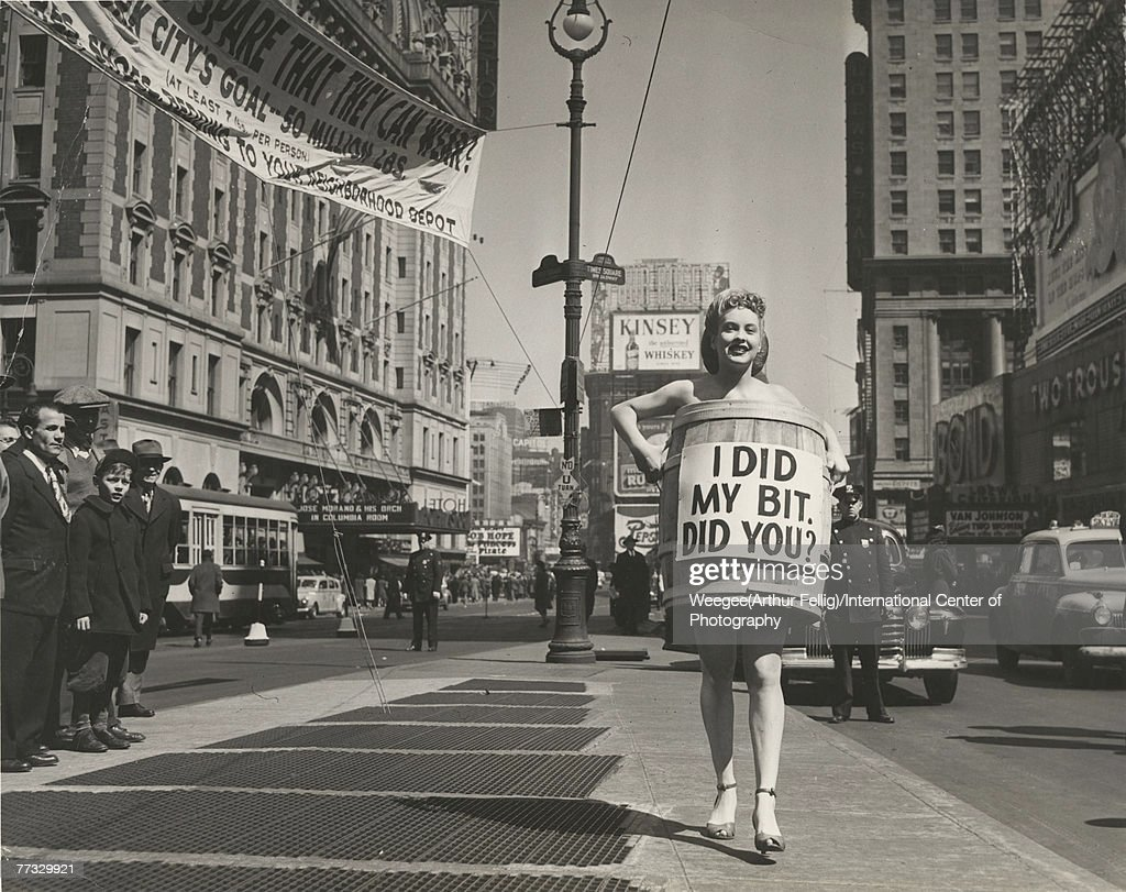 An unidentified woman, dressed in high heels and a wooden barrel that reads 'I did my bit, did you?' walks in Times Square to advertises a nationwide, monthlong drive to collect clothing and bedding for overseas war relief, New York, New York, April 1945. The drive, organized by the United National Clothing Collection, gathered more than 25 million pounds of clothing to be sent to victims of the World War II in Europe. Visible in the background are advertisments for Four Roses, Kinsey Whiskey, and Pepsi-Cola, several movie theatre marquees (including the Loews Critereon, which advertises 'Between Two Women,' and one which advertises The Princess & the Pirate'), the Hotel Astor (at left), and the Bond clothing store (at right). (Photo by Weegee(Arthur Fellig)/International Center of Photography/Getty Images)