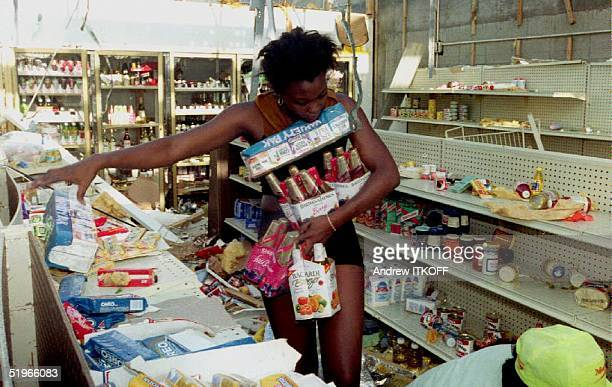 An unidentified woman grabs goods from the shelves of a convenience store 25 August 1992 as looters continued to rob stores damaged by Hurricane...