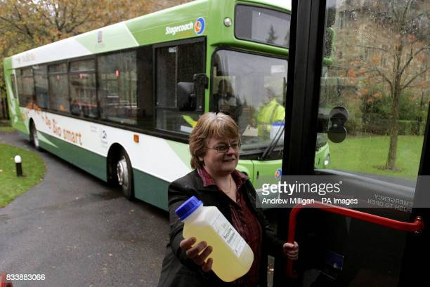 An unidentified woman holds a container which will be handed to passengers on buses for them to fill with cooking oil in return they will receive...