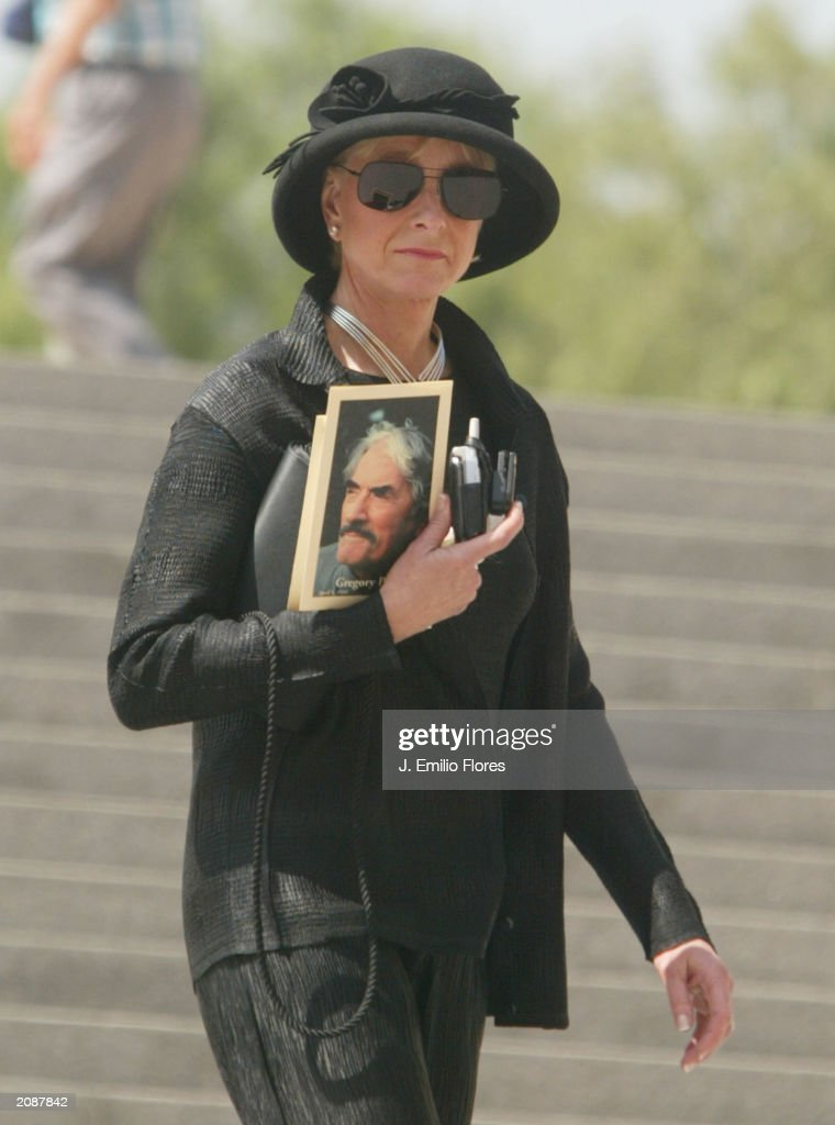 An unidentified woman holds a photograph of Gregory Pecks as shw leaves the Mass Memorial for the actor June 16, 2003 in Los Angeles, California. The public memorial mass was held a the Our Lady of Angels Cathedral in Downtown Los Angeles.