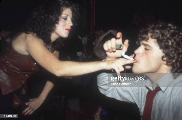 An unidentified woman in a brown leather vest holds a makeshift pipe for a man in a shirt and tie who holds a butane lighter at the nightclub Studio...