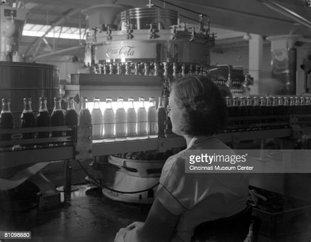 An unidentified woman inspects bottles of CocaCola brand soda on a conveyor belt as they pass before a bright light Cincinnati Ohio 1940s