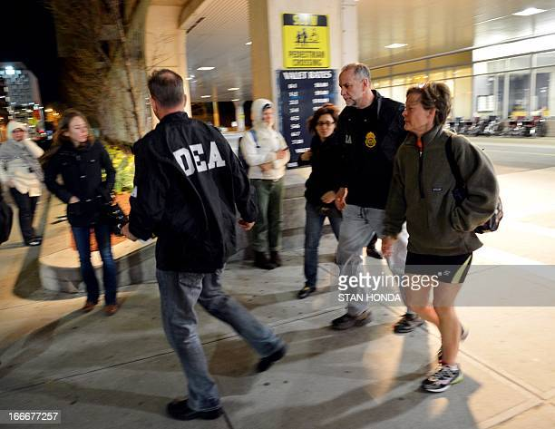 An unidentified woman is escorted by Drug Enforcement Agency agents from the main entrance to Brigham and Women's Hospital April 15 2013 in Boston...