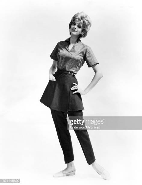 An unidentified woman models a pair of denim slacks with a wraparound skirt stitched into the waistband and a printed calico blouse as she poses...