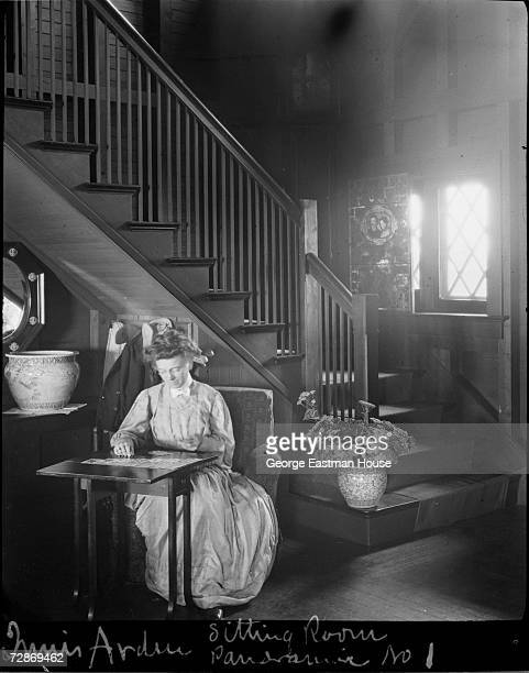 An unidentified woman plays solitaire at a folding table at the foot of a staircase in Innis Arden Greenwich Connecticut 1907 The mansion was built...