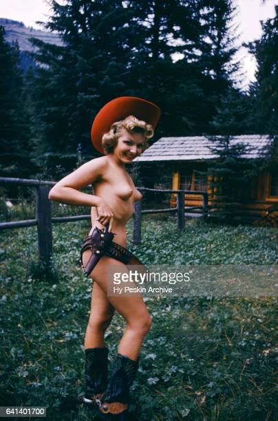 An unidentified woman poses for a portrait in the nude while wearing only a hat boots and a gun circa 1953 in Oregon