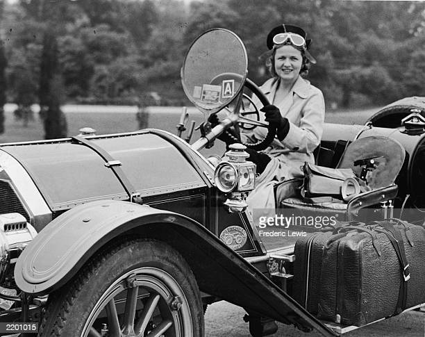 An unidentified woman smiles behind the wheel of a 1914 Mercer automobile as she drives with her luggage strapped to the running board Connecticut...