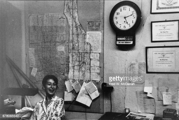 An unidentified woman smiles in the offices of the Village Voice New York New York August 10 1960