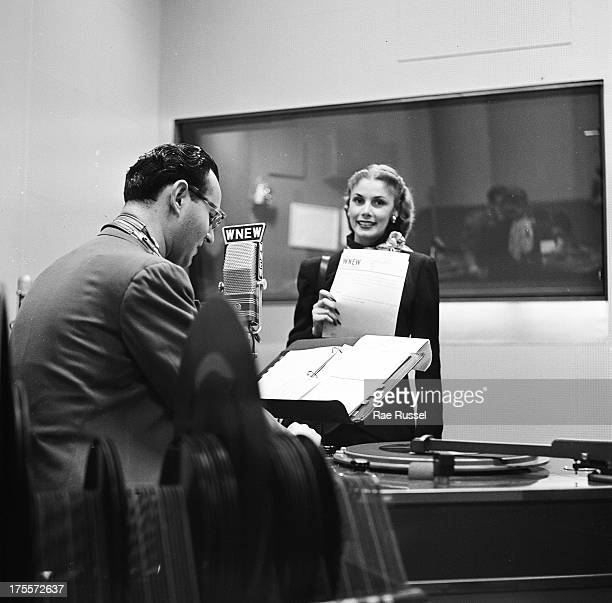 An unidentified woman stands inside the WNEW radio station booth while the radio DJ prepares for a broadcast New York New York 1948