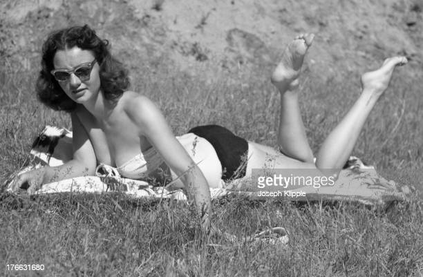 An unidentified woman sunbathes on a blanket on the grass Fort Collins Colorado 1945 She wears sunglasses and a bikini top