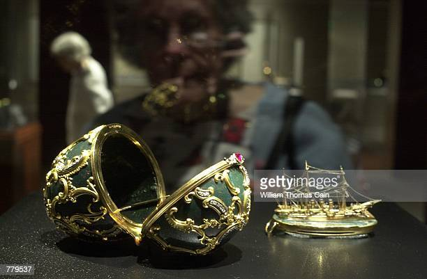 An unidentified woman views a Faberge Easter Egg Box and a Faberge box in the shape of a ship part of the Faberge Collection on display at the First...