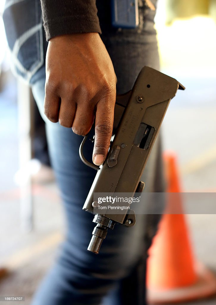 An unidentified woman waits in line with a MAC-9 semi-automatic pistol at a gun buy back program at the First Presbyterian Church of Dallas on January 19, 2013 in Dallas, Texas. The gun buy back program has collected and destroyed over 400 pistols, rifles, shotguns and semi-automatic assault weapons since its inception. U.S. President Barack Obama recently unveiled a package of gun control proposals that include universal background checks and bans on assault weapons and high-capacity magazines.