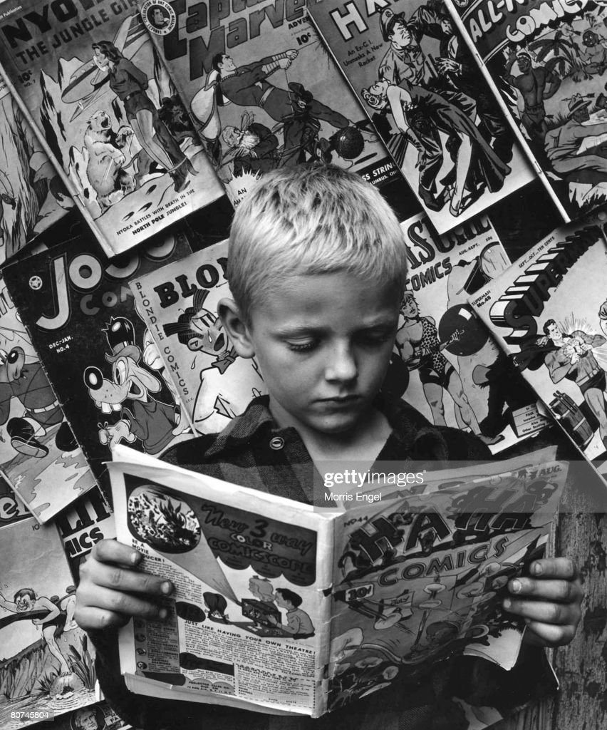 An unidentified young boy ina checkered shirt reads an issue of Ha Ha Comics as he stands before a wall of other comics, New York, New York, 1946. Other visible titles include Nyota the Jungle Girl, Captain Marvel, Blondie, and Superman.