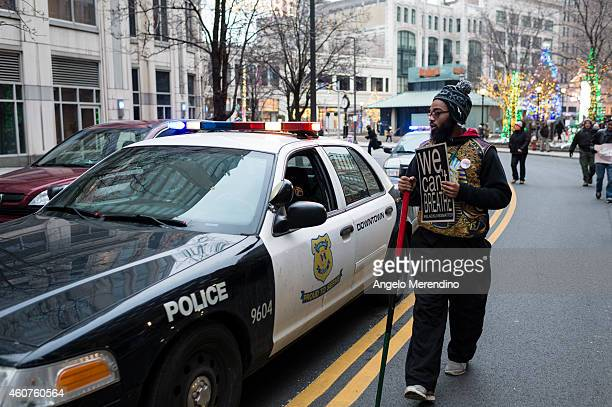 An unidentified young man walks next to a police cruiser on Prospect Ave December 21 in Cleveland Ohio Protestors from Ferguson Missouri travelled to...