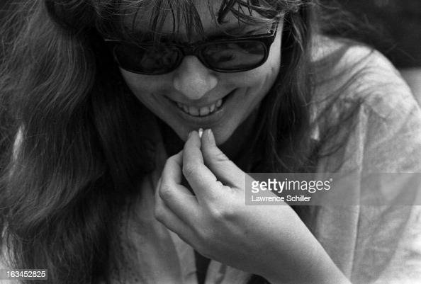 An unidentified young women smiles as she moves to take LSD capsule California 1966