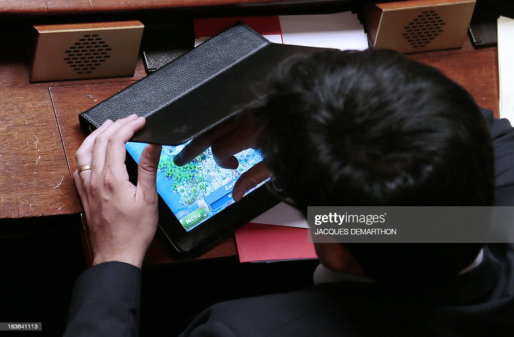 An unidetified MP plays video game during a weekly session of the questions to the government on October 8, 2013 at the National assembly, in Paris.