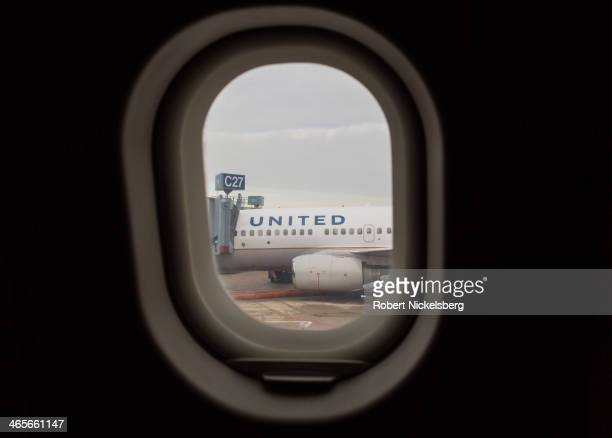 An United Airlines plane is viewed through a plane window January 17 2014 at O'Hare Airport in Chicago Illinois