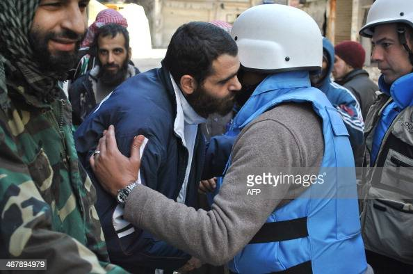 An United Nations World Food Programme worker is welcomed by a rebel fighter on February 8 2014 on the second day of a humanitarian mission in a...