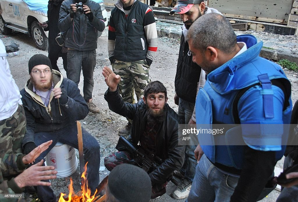 An United Nations World Food Programme worker talks with rebel fighters on February 8 2014 on the second day of a humanitarian mission in a besieged...