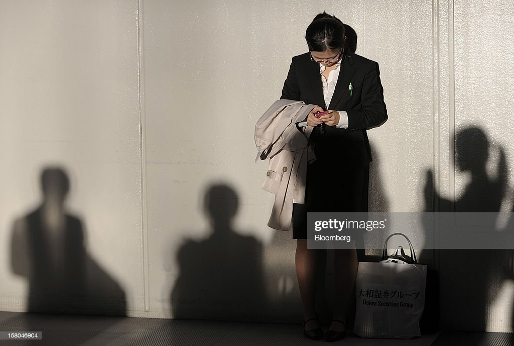 An university student, uses her smartphone at a job fair hosted by Mynavi Corp. in Tokyo, Japan, on Saturday, Dec. 8, 2012. In Japan, many students accept job offers from large companies six months before graduating and may stay with the same employer until retirement, said Yoshihide Suzuki, an administrative director at the career center at Waseda University. Photographer: Akio Kon/Bloomberg via Getty Images