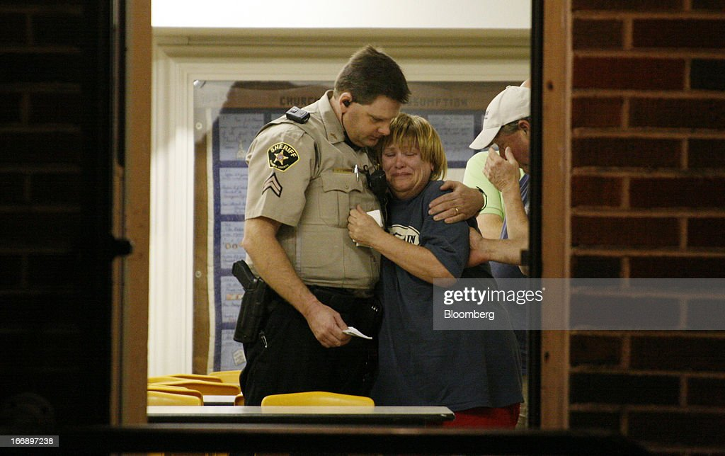 An unknown woman is consoled by a Sheriff's Deputy at a command post in West, Texas,U.S., on Thursday, April 18, 2013. An explosion at Adair Grain Inc.'s fertilizer facility in the town of West, Texas, killed as many as 15 people and injured at least 160 in what may be the worst U.S. industrial disaster since the Texas refinery blast in 2005. Photographer: Mike Fuentes/Bloomberg via Getty Images