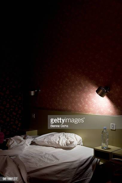 An unmade bed illuminated by a lamp at night