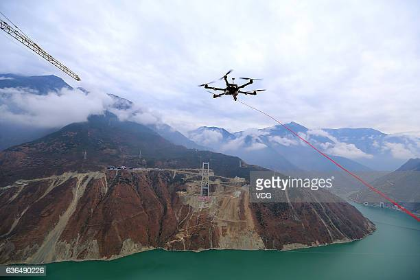 YA'AN CHINA DECEMBER 20 An unmanned aerial vehicle towing a cable flies over the Dadu River to another side of the Ya'anKangding expressway bridge...