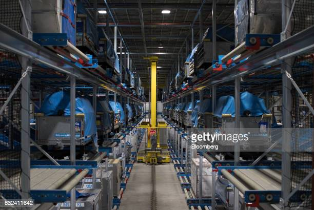 An unmanned mail sorting vehicle collects packages as cargo crates stand on shelving inside the KLM Cargo center operated by Air FranceKLM Group at...