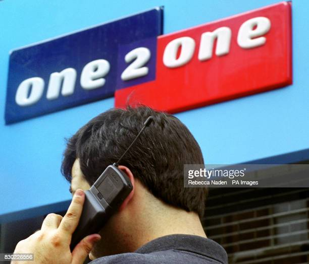 An unnamed mobile phone user outside a shop in London selling One2One mobile phones Telecoms group Cable Wireless and MediaOne of the US announced...