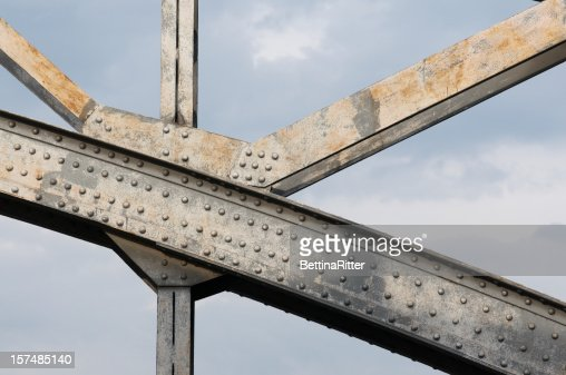 An up close image of the beams holding up a steel bridge