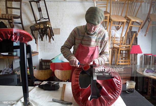 An upholstery business owner recovering a chair