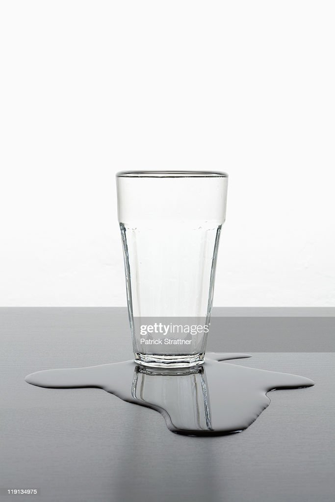An upright glass standing in a puddle of spilled water