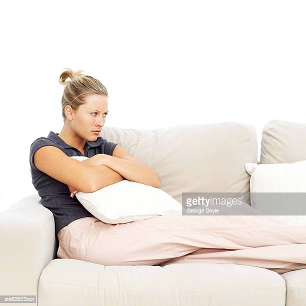 an upset young woman sitting on a couch holding a cushion