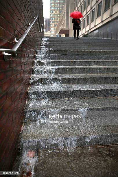 An urban waterfall forms on the steps of City Hall Plaza in Boston from the heavy rainfall leaving Danielle Worthen from Boston to navigate the...
