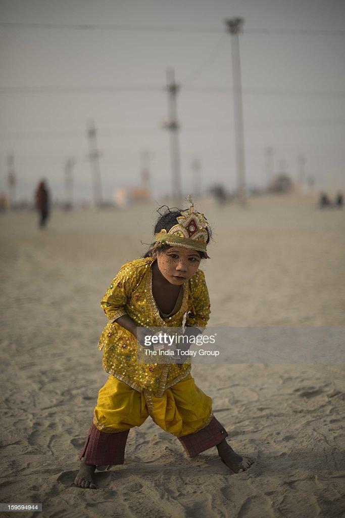 An urchin dressed like a Hindu god asks for money near the Sangam, Allahabad during the Mahakumbh.