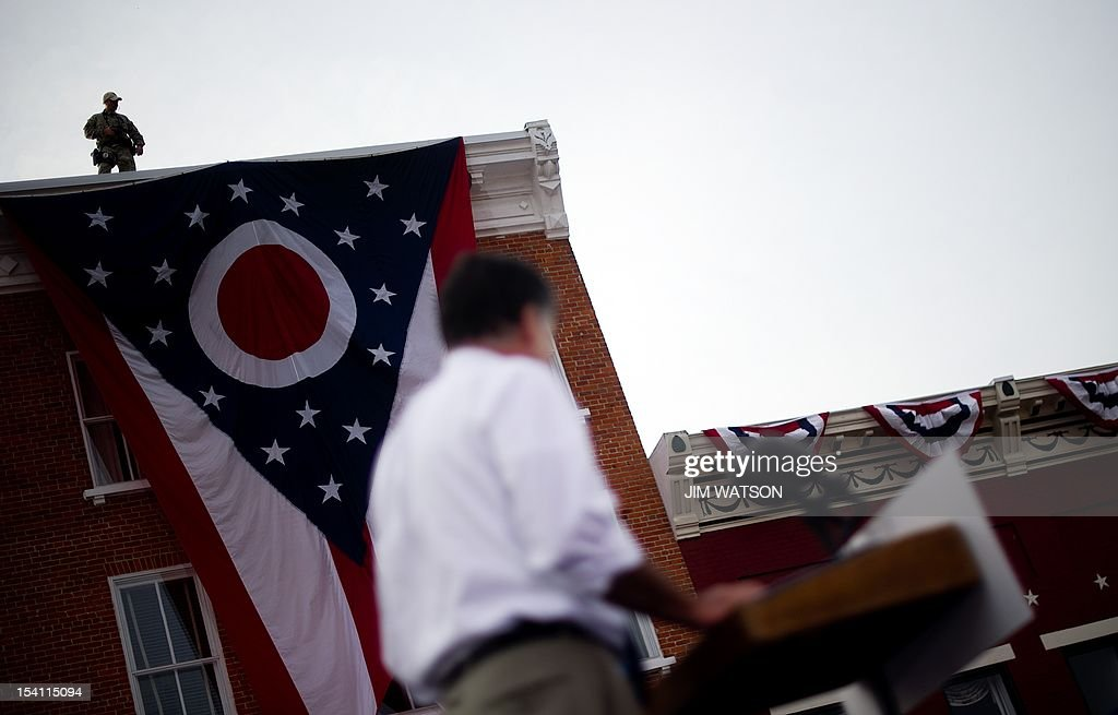 An US Secret Service agent stands lookout from atop a building as US Republican presidential candidate Mitt Romney (C) delivers remarks at a victory rally Lebanon, Ohio, October 13, 2012. As the election draws nearer, the press pool and staff member work around the clock in plain sight, as well as behind the scenes, as US Republican Presidential candidate Mitt Romeny travels across the country to deliver his message. AFP PHOTO/Jim WATSON