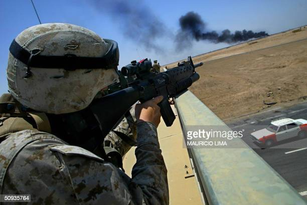 An US soldier from 2nd Battalion 1st Marines takes position on a bridge over a highway inspecting a plume of black smoke on the outskirts of the...
