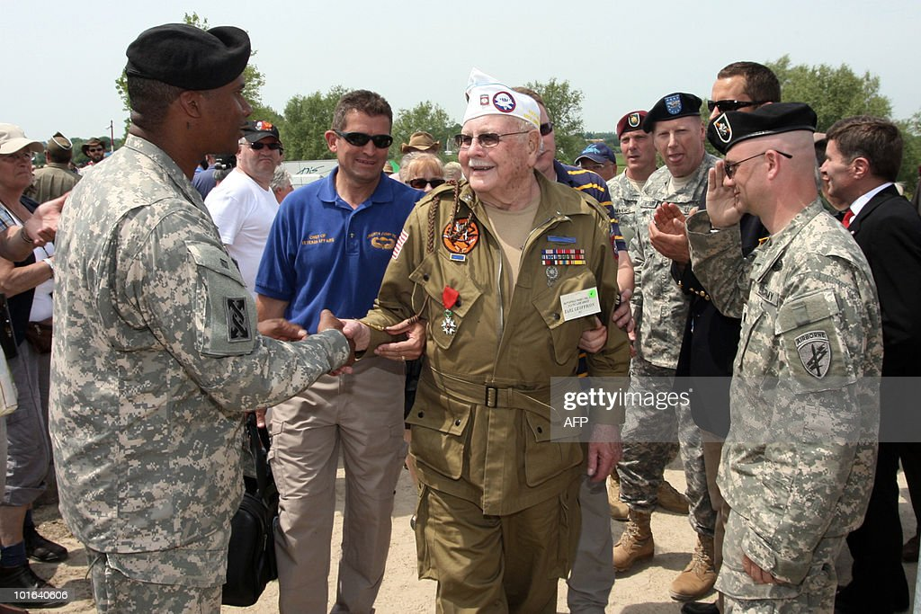 An US soldier shakes hands with an US veteran of the World War II (C) on June 5, 2010 near Sainte-Mere-Eglise, during the D-Day celebrations to mark the 66th anniversary of the June 6, 1944 allied landings in France. AFP PHOTO KENZO