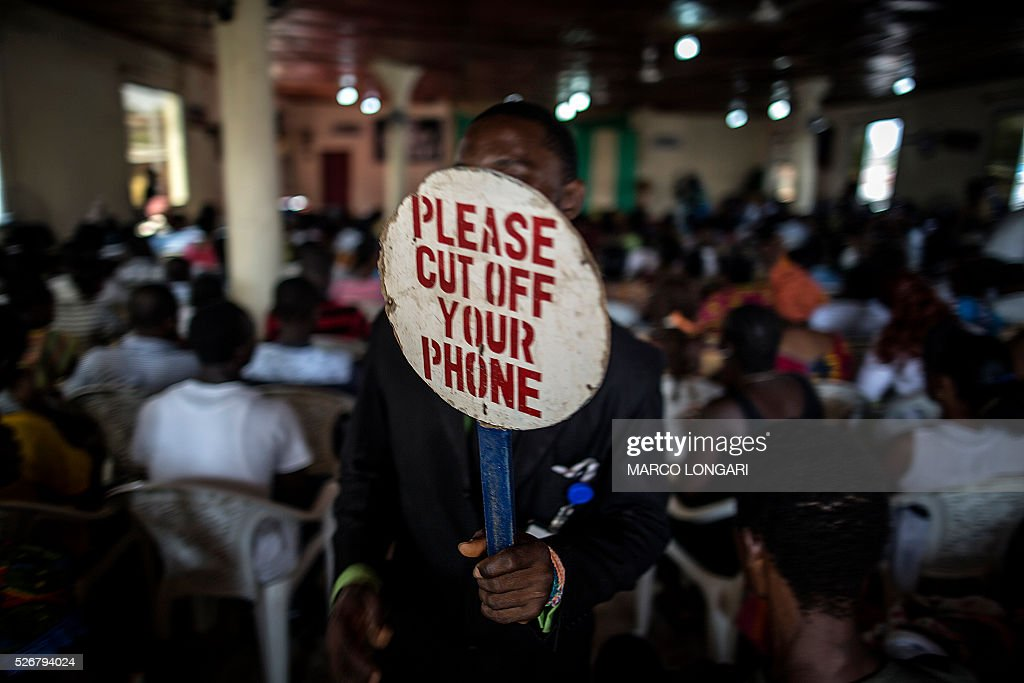 An usher holds a sign as people pray at the Winners Chapel International in the Weasay district of Monrovia on May 1, 2016. / AFP / MARCO